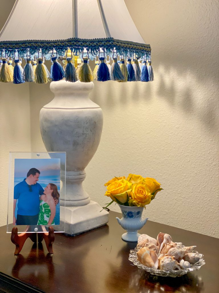 bedside table featuring yellow roses, picture of a couple, bowl of shells and a lamp