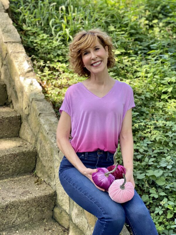 woman wearing WHBM ombre pink jetsetter tee, mott & bow jeans and WHBM espadrille mules and holding 3 pink velvet pumpkins
