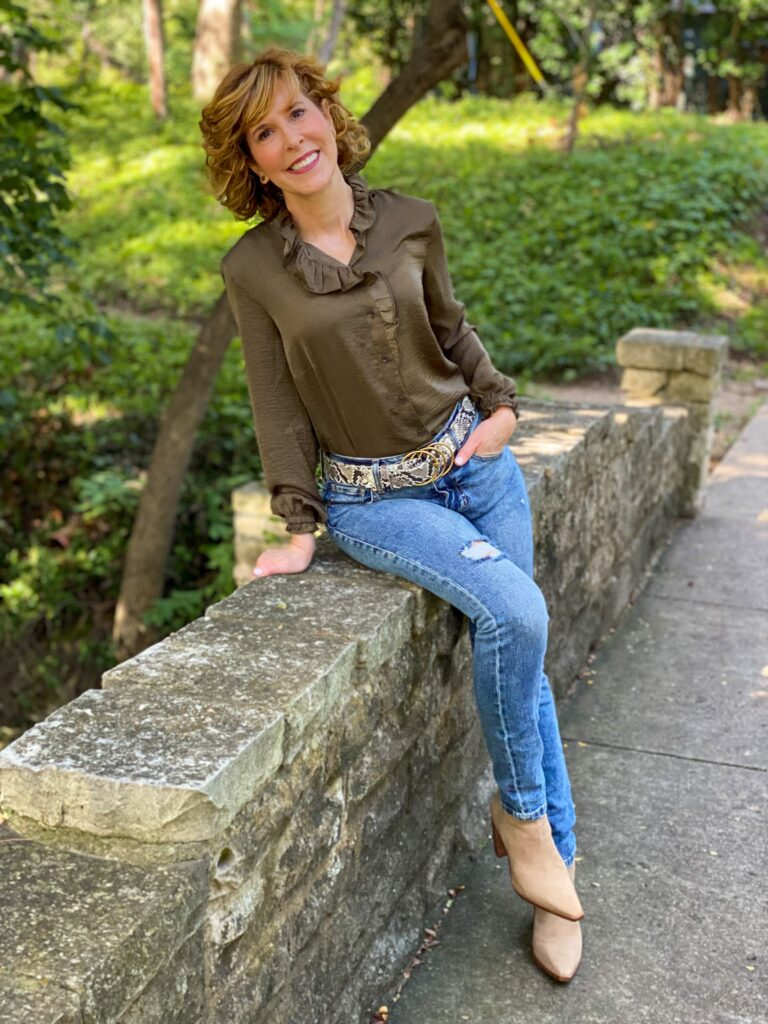 woman wearing cabi icon blouse, cinch skinny, and serpent belt with vince camuto taupe suede booties sitting on the side of a bridge