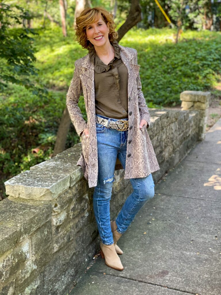woman over 50 standing outside and wearing cabi icon blouse, cinch skinny, serpent belt, and king cobra jacket with vince camuto taupe suede booties