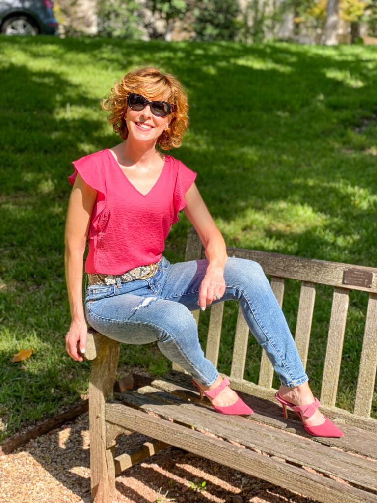 woman over 50 sitting on a park bench wearing cabi cinch skinny jeans, serpent belt, rose top, cheeky topper