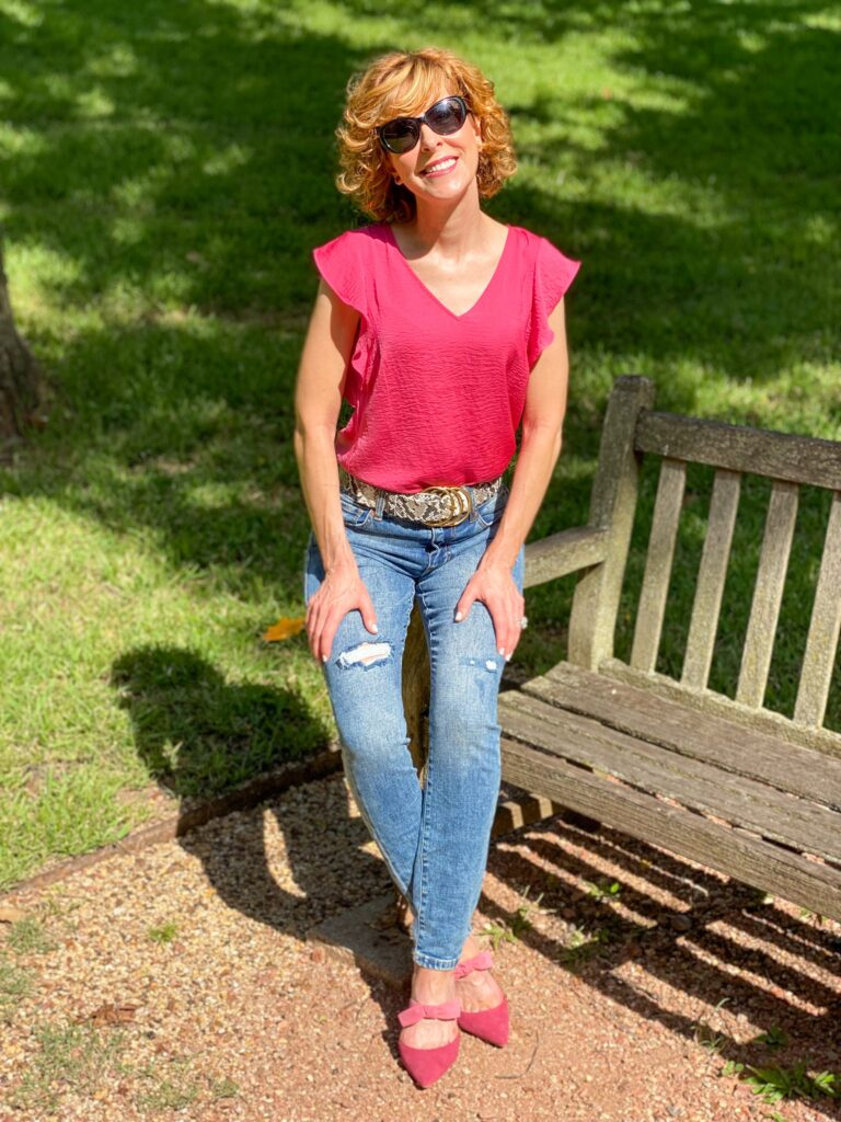 woman over 50 standing near a park bench wearing cabi cinch skinny jeans, serpent belt, rose top, cheeky topper