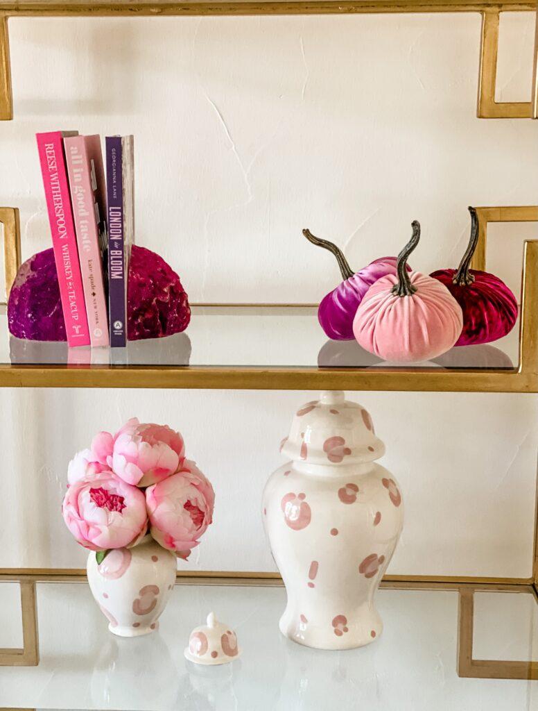 woman's office decor shelves pink pumpkins, pink ginger jar, pink books, pink geode bookends, pink peonies
