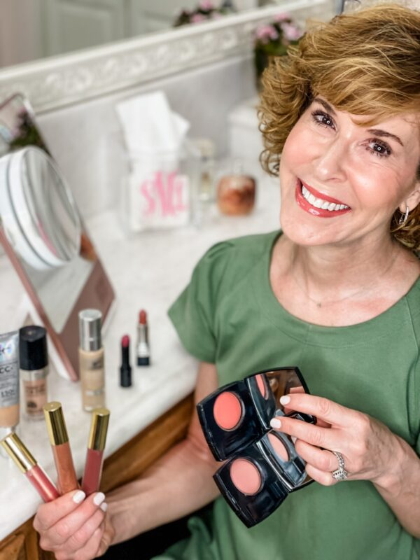 woman in green dress sitting in a white bathroom surrounded by makeup products