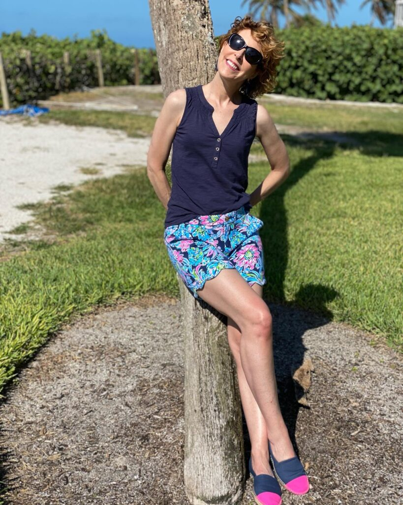 woman posing by a palm tree wearing lilly pulitzer sunshine sale items