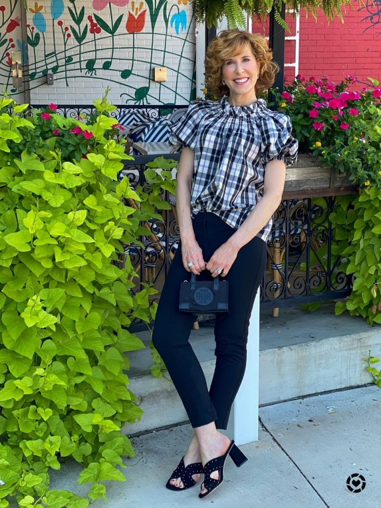 woman wearing jcrew plaid puff sleeve blouse and black pants leaning back against a pole carrying a tory burch micro bag