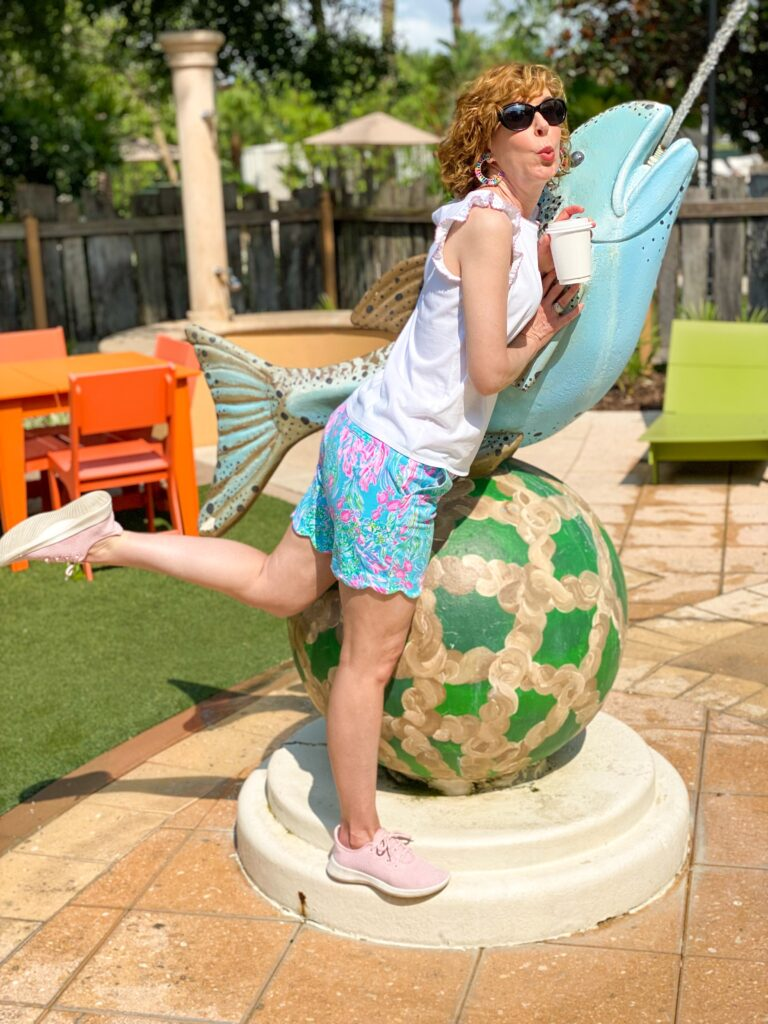 woman posing by a fish spouting water wearing lilly pulitzer sunshine sale items