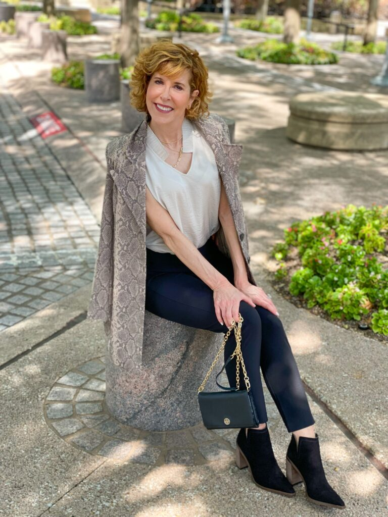 woman over 50 sitting and wearing cabi dinner trousers, cabi king cobra jacket, cabi snapshot top