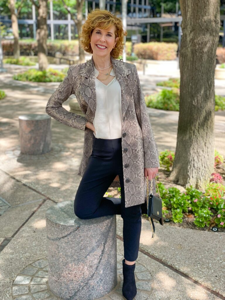 woman over 50 standing and wearing cabi dinner trousers, cabi king cobra jacket, cabi snapshot top