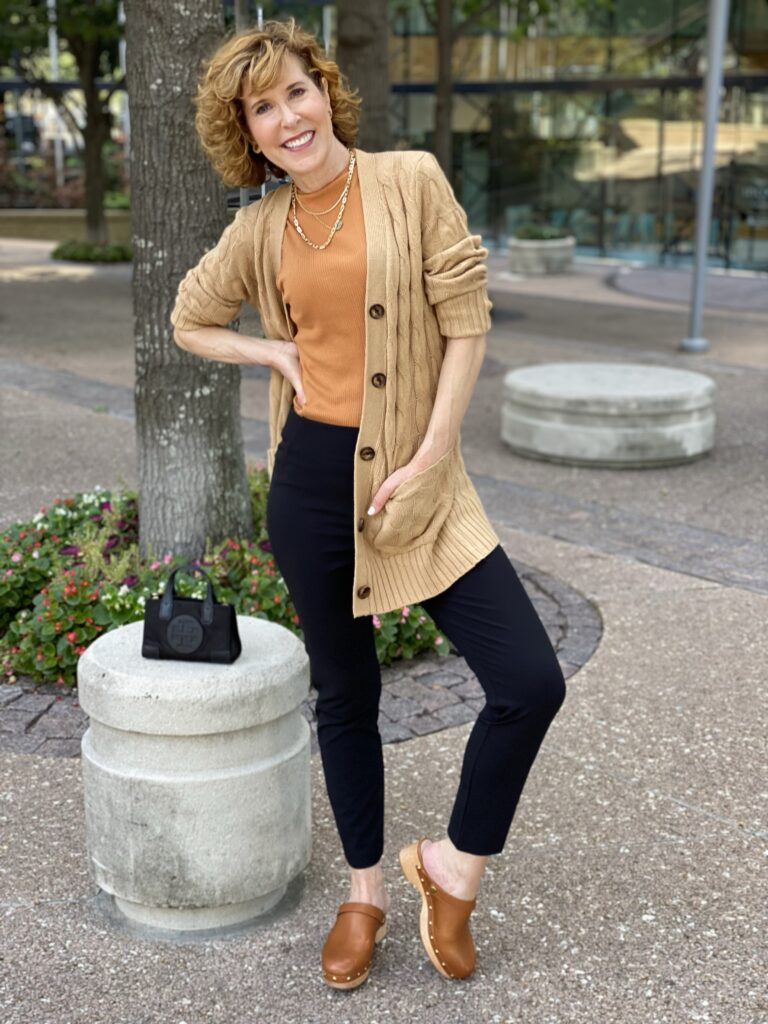 woman wearing black pants, brown clogs, a rust mock tank, and a tan cardigan with a tory burch micro ella tote bag besider her