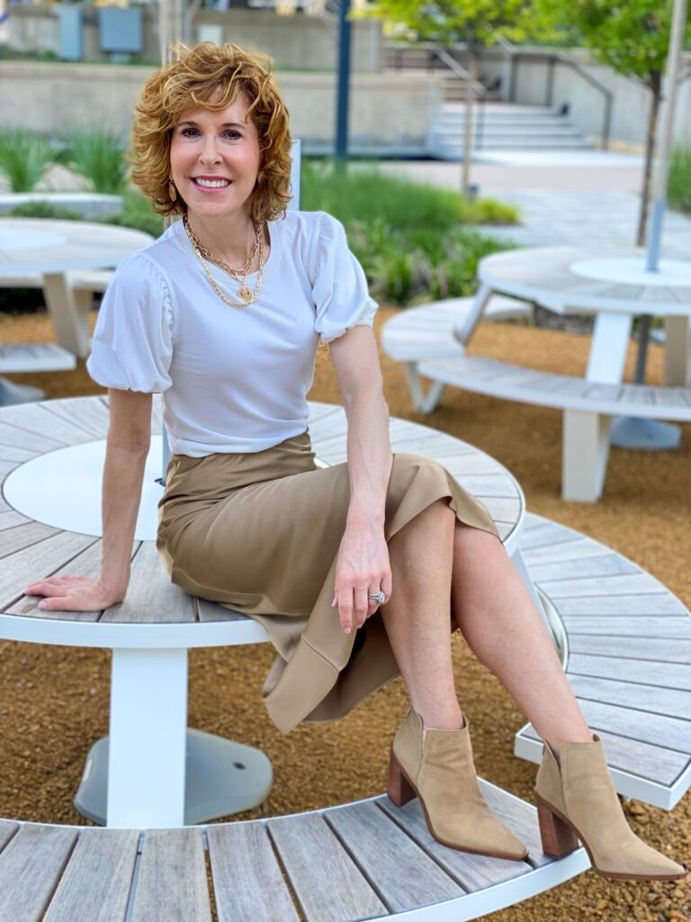 woman wearing puff sleeve tee with tan slip skirt and tan booties sitting on a table