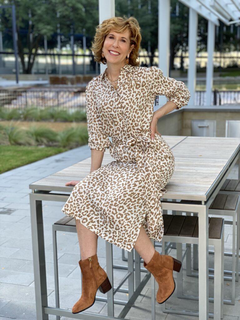 woman wearing jcrew animal print shirtdress sitting on a table