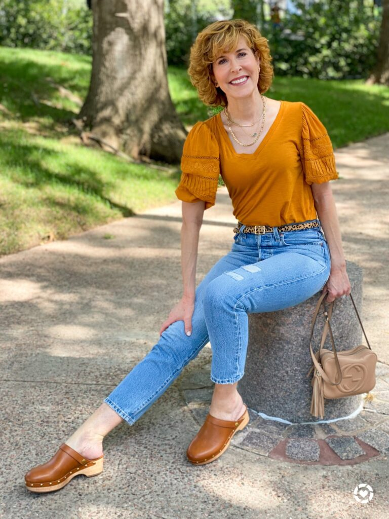 woman wearing loft gold puff sleeve top and levi's distressed jeans with clogs