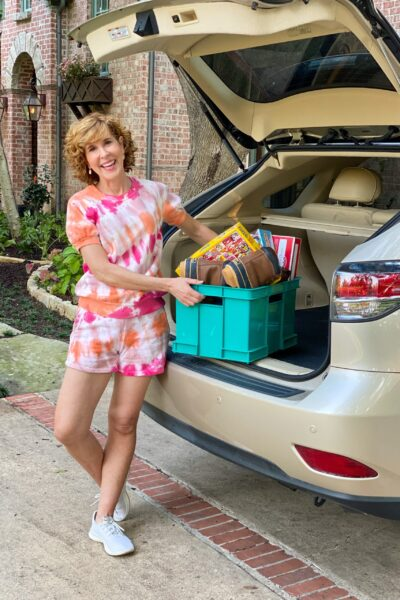 woman wearing tie dye outfit standing near the trunck of her car with box of things to donate