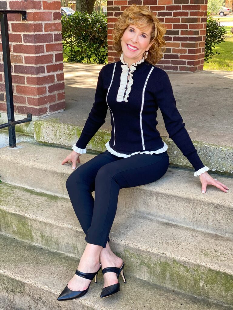 woman over 50 sitting on stairs wearing cabi adorn pullover and dinner trousers