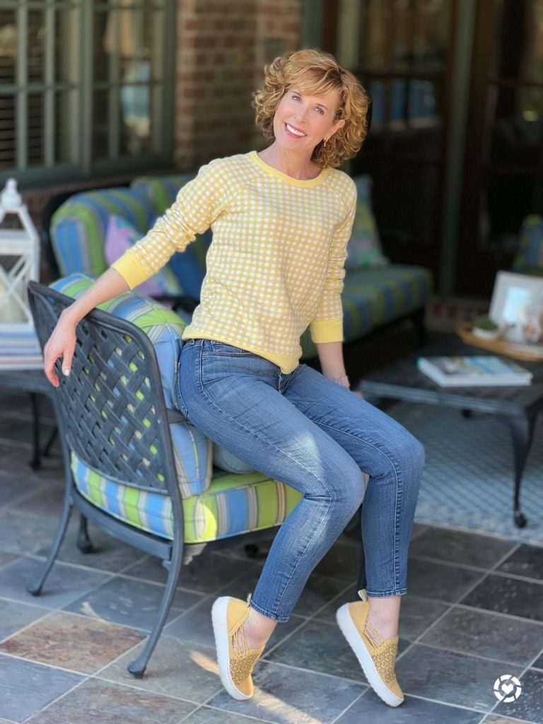 woman wearing draper james yellow gingham sweatshirt nydj distressed jeans and jambu erin sneakers sitting on the armrest of a chair on a patio