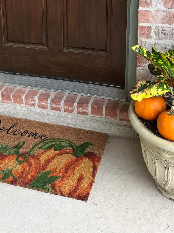 Pumpkin doormat and fall planter sitting by a backdoor