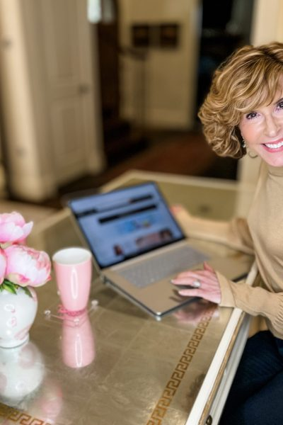 Woman sitting at desk looking at amazon premium beauty page on laptop