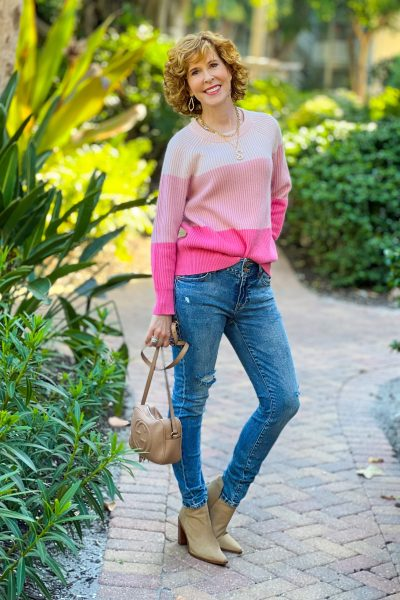 over 50 woman wearing jcrew pink ribbed cashmere relaxed crewneck sweater in colorblock and distressed Levi jeans with taupe suede booties holding a Gucci purse standing on a brick path