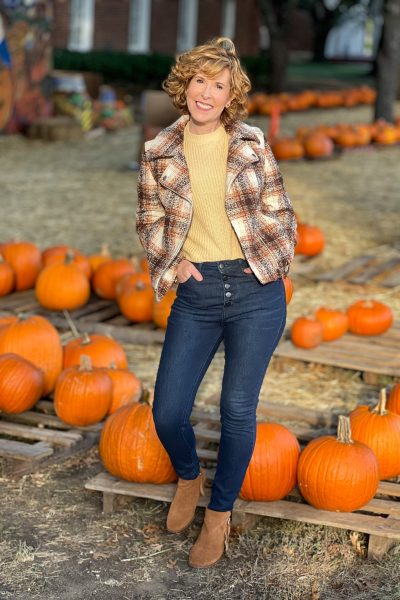 woman over 50 wearing nordstrom treasure & bond plaid moto jacket, nordstrom bp cleo crewnneck sweater, nordstrom halogen, bp button front skinny jeans standing in a pumpkin patch